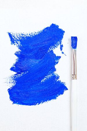 Blue color 2020. Oil paint strokes on white background and brush. Art background. Vertical photo