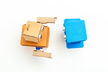 Two robots are talking. Cardboard and plastic robot on white background. Flat lay Imagens