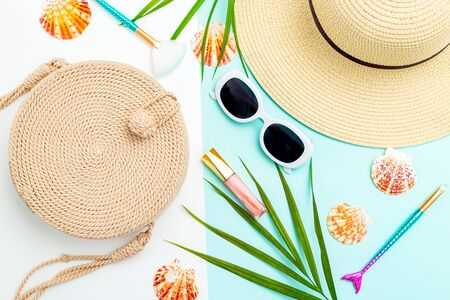 Travel accessories. Wicker handbag and wicker hat on a blue and white background. Flat lay