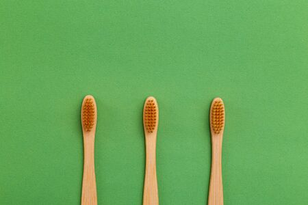 Wooden Toothbrush on gren background. Reusable. Minimalist concept Stock Photo