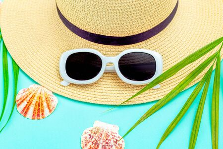 Travel.  Ð«traw hat and  white  sunglasses on mint background. Tropical