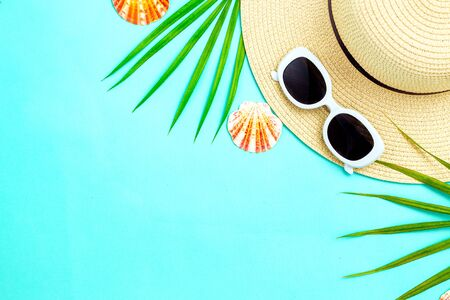 Travel. Feminine white  sunglasses and straw hat on mint background. Copy space