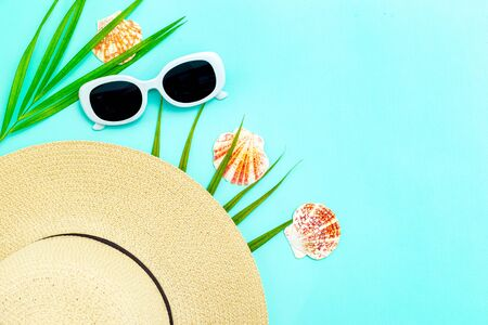 Travel feminine accessories. White  sunglasses and straw hat on blue background. Copy space Imagens - 137486133