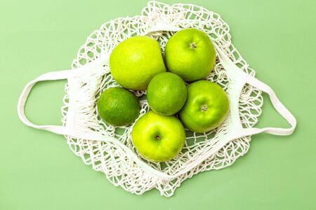 Net bag with green fruits on a green background. Zero waste. Monochrome green.