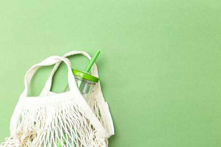 Glass bottle and net bag on a green background. Copy space. Monochrome. Zero waste