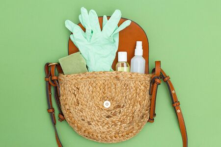 Antiseptic and rubber gloves in wicker handbag on green background. Disinfection. Flat lay
