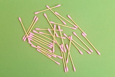 Bamboo cotton buds with pink cotton on a green background. Natural elements. Zero waste. Flat lay Zdjęcie Seryjne