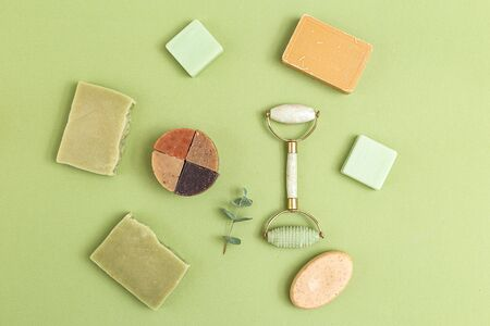 Natural soap and face roller on geen background. Self-care. Flat lay Zdjęcie Seryjne