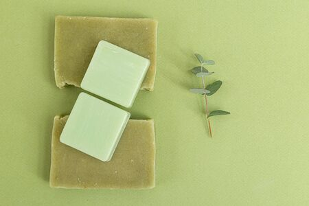 Natural soap and  eucalyptus on green background. Self-care. Green monochrome. Minimalism