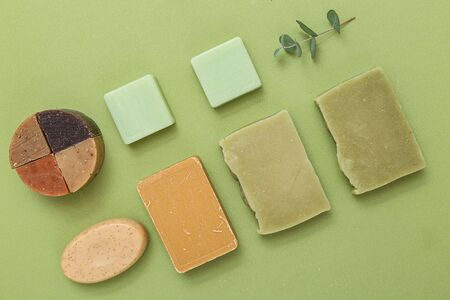 Natural soap of different shapes and a sprig of eucalyptus on a green background. Undertone. Self-care