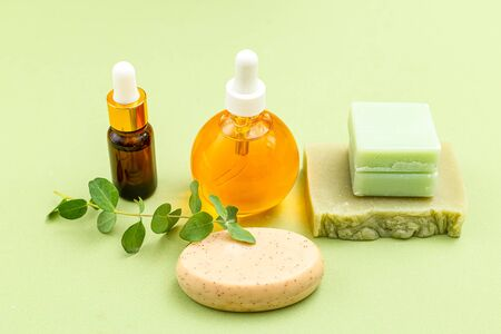 Natural soap and eucalyptus with serum on green background. Monochrome;