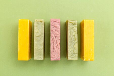 Natural soap of different colors of a rectangular shape on a green background. Flat lay. Abstraction