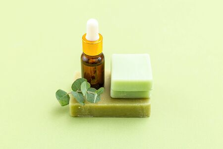 Soap, eucalyptus and serum on green backgriund. Skin care. Minimalism 스톡 콘텐츠