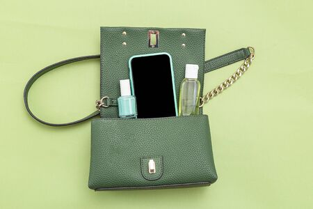 Handbag, phone, nail polish  and disinfection; gel on green background. Monochrome. Minimal.  Imagens