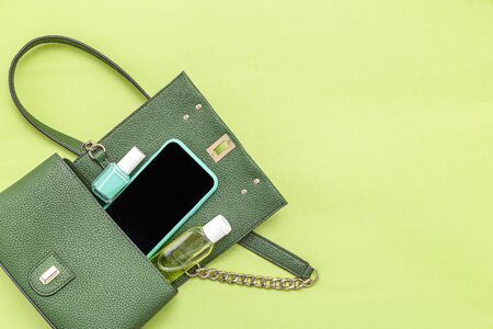 Handbag, phone, nail polish  and disinfection; gel on green background. Monochrome. Minimal. Copy space Imagens