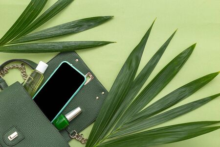 Handbag, phone, nail polish and natural leaves on green background. Monochrome пкуут. Copy space