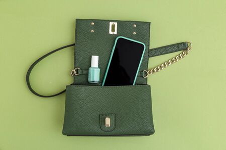 Handbag, phone, nail polish green color. Monochrome. Minimal