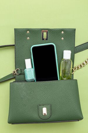 Handbag, phone, nail polish  and disinfection; gel on green background. Monochrome. Minimal.  Vertical format