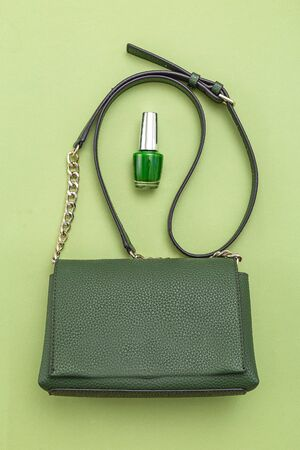Handbag green color and nail polish on green background.  Monochrome. Vertical format.  스톡 콘텐츠
