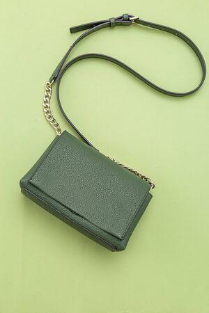 Handbag green color on green background.  Monochrome. Vertical format