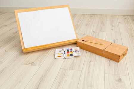 Wooden easel and sheet of paper with watercolor paint. Contented Emotion. Art 스톡 콘텐츠 - 150073333