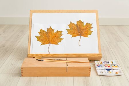 Wooden easel and maple leaf pattern  watercolor paint. Contented Emotion. Art