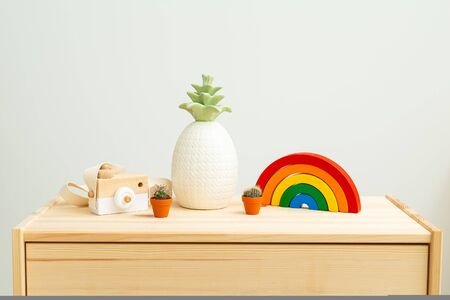 Children's wooden toys rainbow and Houseplant on wooden shelf. Zero waste. Decoration