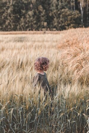Little girl s in a wheat field. Back to nature. Reconnecting with nature. Vertical format