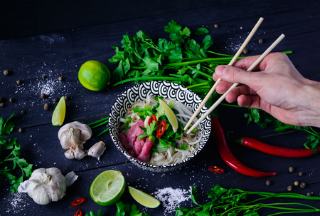 Pho Bo vietnamese soup with noodles, beef, chili pepper, onion,  cilantro and lime on dark blue wooden background with hand