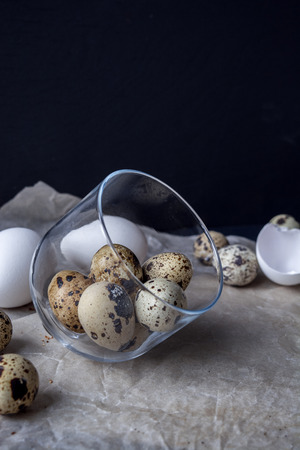 Quail eggs and chicken eggs. White paper background. Top view. Free space.