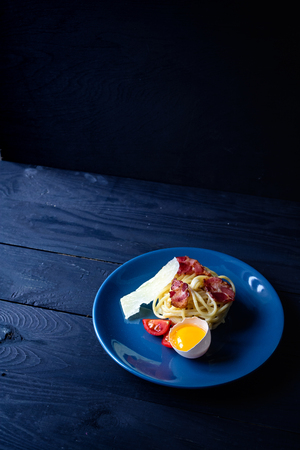Pasta carbonara on a table with fresh products on dark background, copy space, food background Stock Photo