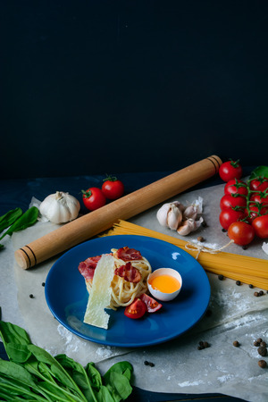 Italian pasta carbonara on a blue plate food background, table with fresh products, copy space