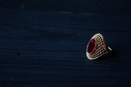 Golden ring with red stone isolated on a black background
