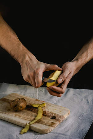 The chef cleans potatoes. For dishes with potatoes. On a black background, the concept of the menu, cooking, healthy eating Фото со стока