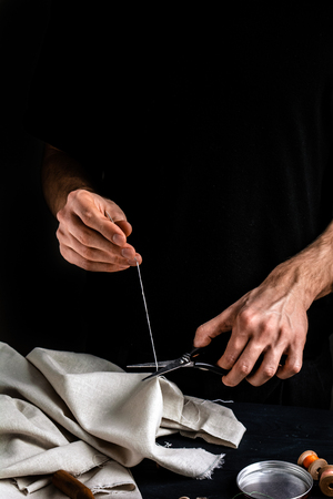 Tailor cutting a thread with scissors, close up, black background