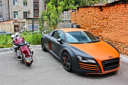 Oekraïne, Kiev; 20 augustus 2013; Audi R8 ABT en Honda-motorfiets. Rood. Oranje. Chromium. Op muur achtergrond. Tuning. Redactionele foto.