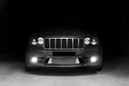 January 3, 2011. Kharkov, Ukraine. Jeep Grand Cherokee SRT8 in the shadows with glowing lights in low light. Brutal off-road car in the shade. Black and white photo. Editorial