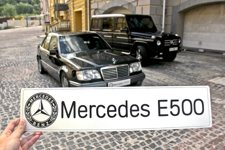 June 30, 2013, Kyiv. The guy holding the sign Mercedes E500 on the background of Mercedes. Mercedes-Benz W124 E500 Wolf and Mercedes-Benz G55 AMG. Editorial photo. 新聞圖片
