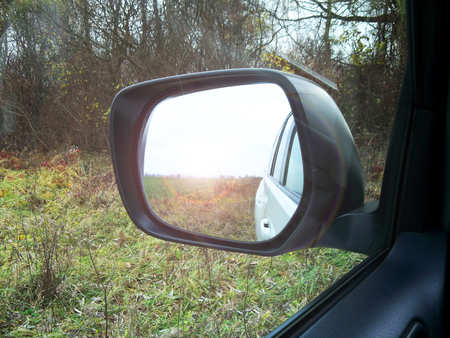 Reflected in a rearview. In the background forest. Autumn. Winter. Car. Nature. Sun