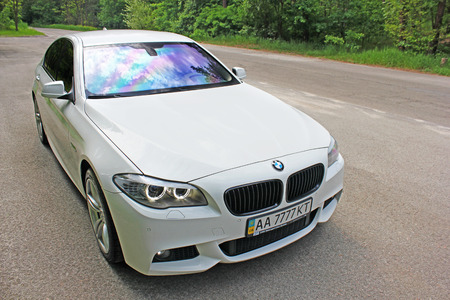 White BMW 520 TDI (F10) M Sport in the forest road. Kiev, Ukraine. May 17, 2014. Editorial photo.