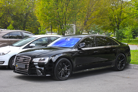 Kiev, UA - May 3, 2017: Audi A8, A black prestigious car parked in a parking lot against a backdrop of bushes