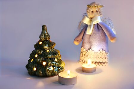 Christmas arrangement. Christmas angel, candles and Christmas tree. Candles burn. Merry Christmas. Happy New Year. Card