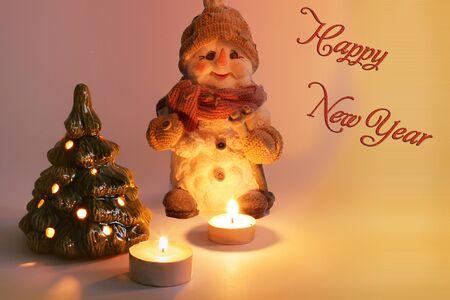 Christmas arrangement. Christmas snowman, candles and Christmas tree. Candles burn. Merry Christmas. Happy New Year. Card Stock Photo