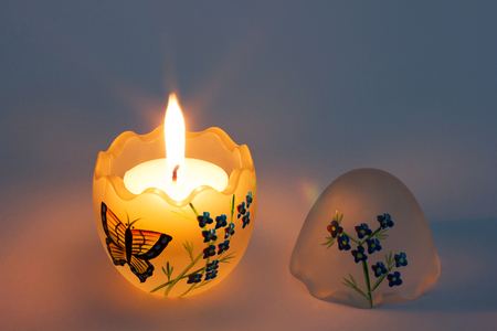 Festive candle burning in a candlestick made of glass. Festive painted egg. Glass egg with painting. Easter egg decorated with a butterfly and flowers Stock Photo