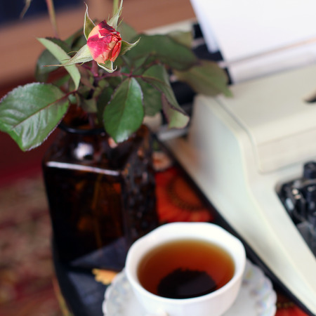 A typewriter, tea and a rose in a vase. Antique table. Romance. Stock Photo