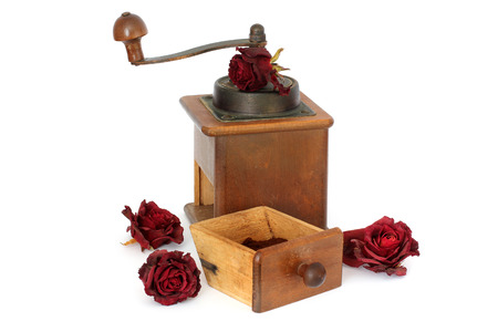 Manual coffee grinder with roses on a white background. Antiquary. Retro. Old things. Coffee Stock Photo