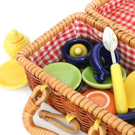 Basket with utensils on a white background. Children's tableware. Stove, spoon and cup Standard-Bild