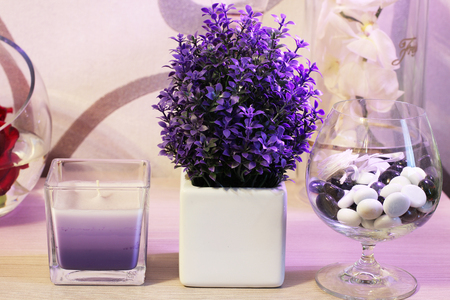 Candle. Violet decorative flowers and stones. Flowers in a vase