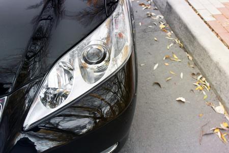 Luxury Headlights. Part of a black car on asphalt background 免版税图像