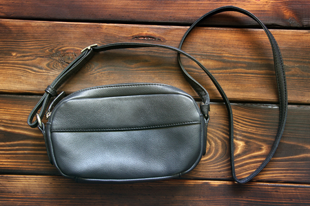 Leather women bag on wooden background